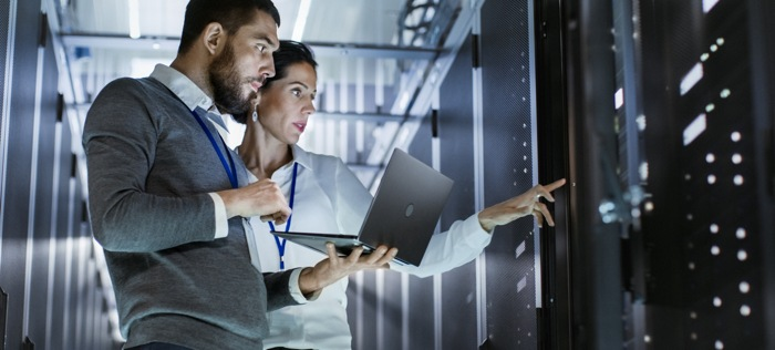 Man and woman looking at rack in a datacenter