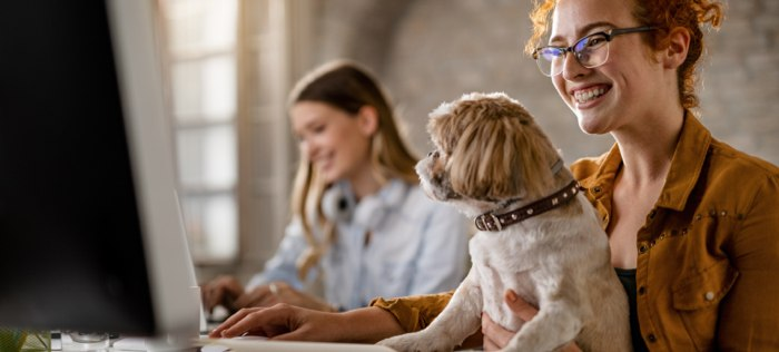 Smiling woman with dog in lap at a computer with woman in the background